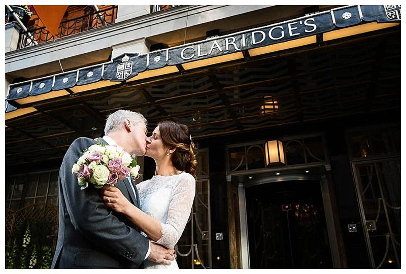 Summer Wedding at Claridge's Bride and Groom kiss by entrance