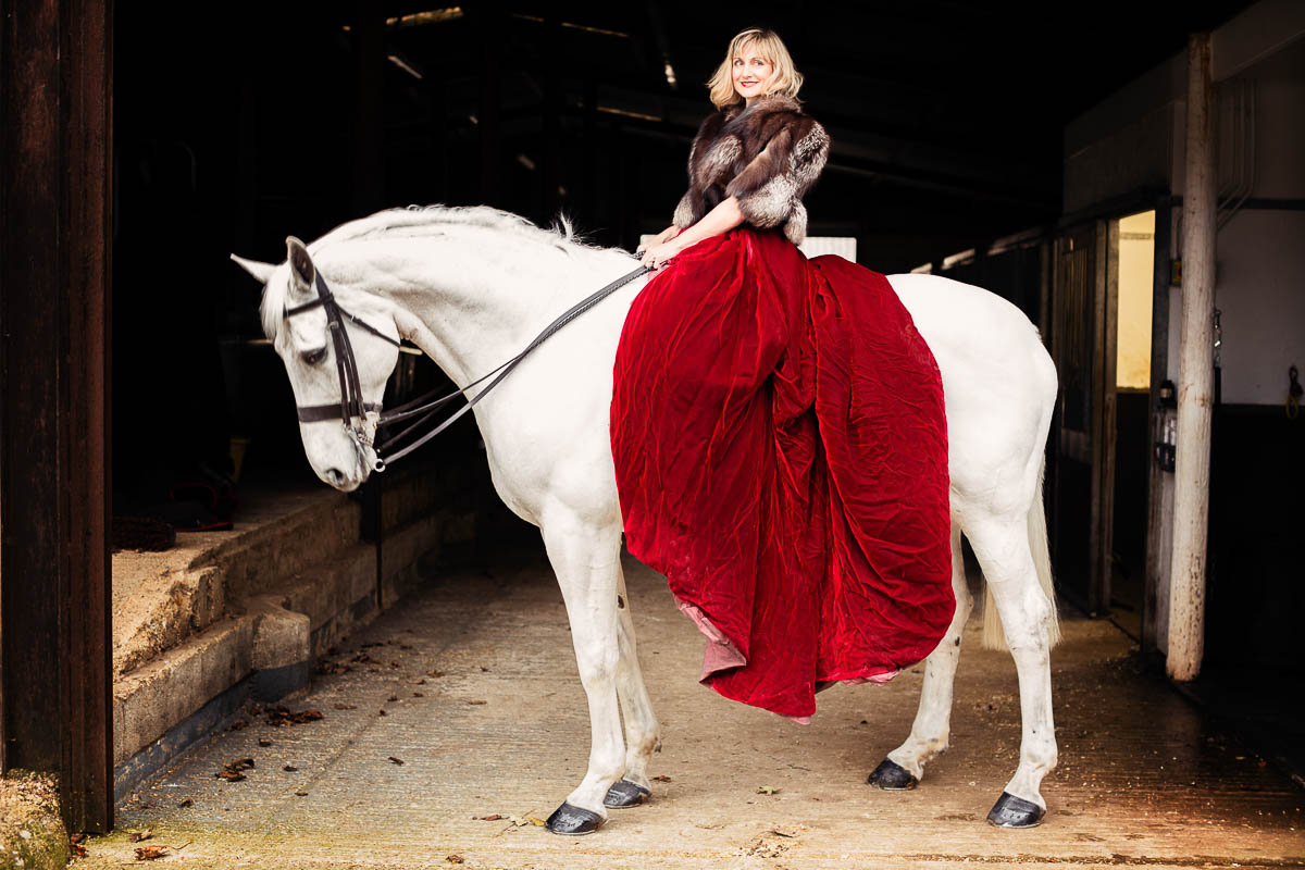 female portrait of a side view of woman in red velvet ballgown on a white horse
