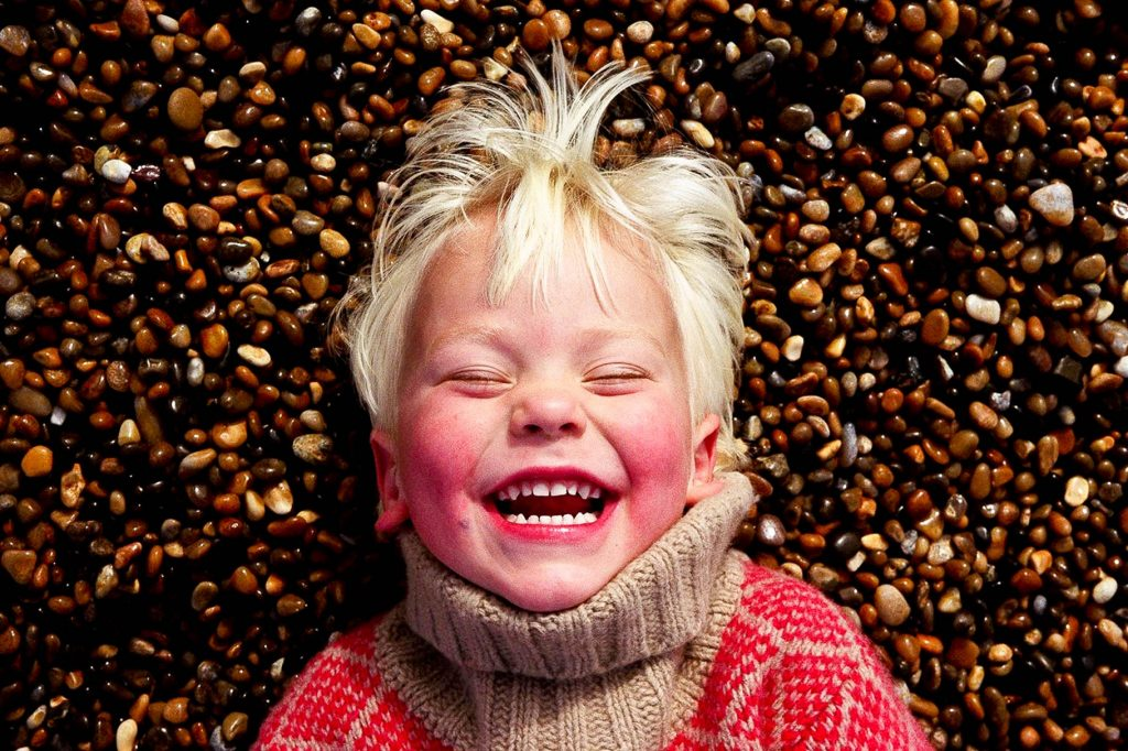 little boy lying on pebbles laughing