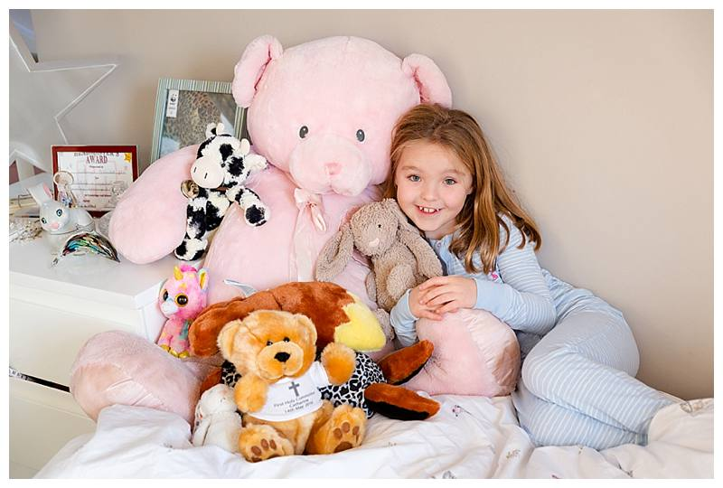 Little girl with lots of teddies
