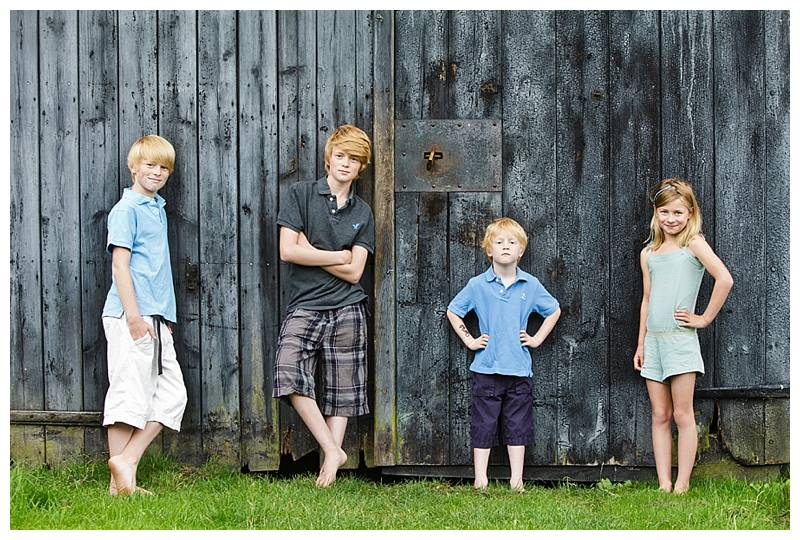 Family photography London four siblings photographed against barn door