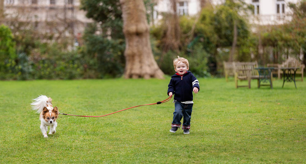 little boy running with dog in park