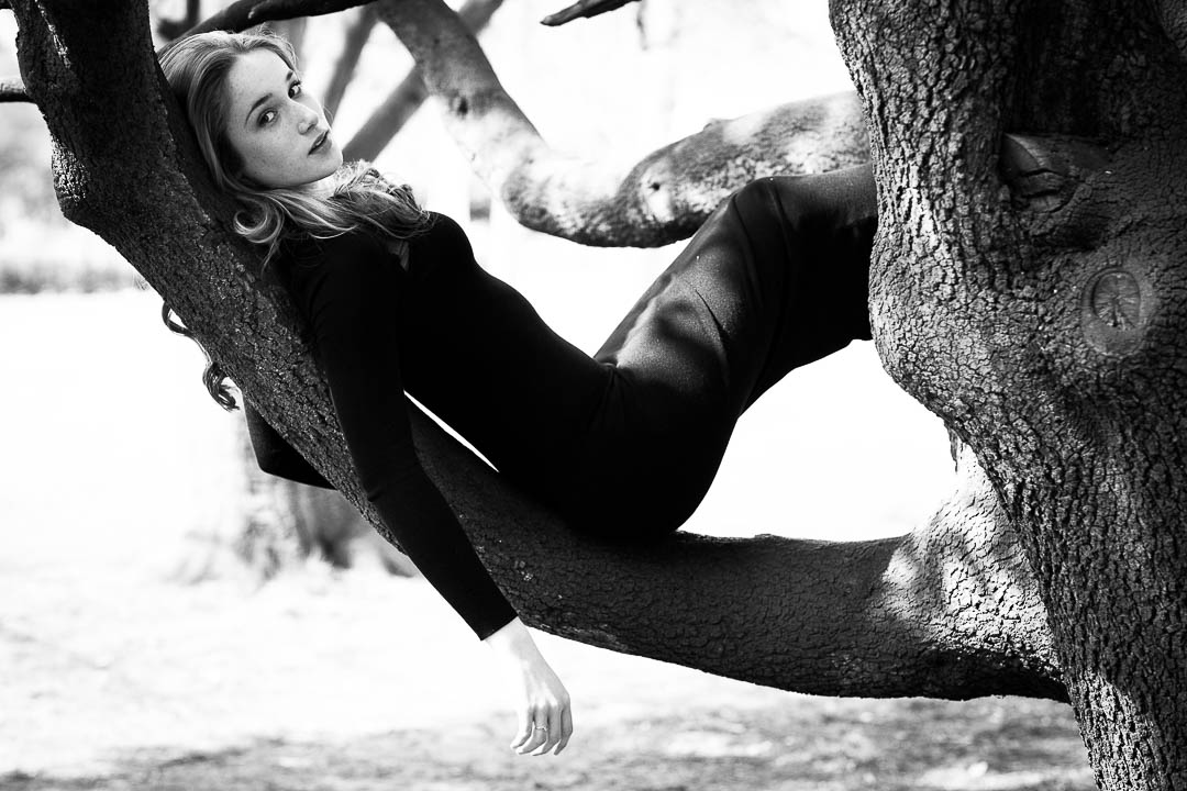 teenage photoshoot girl reclining in tree in west London park