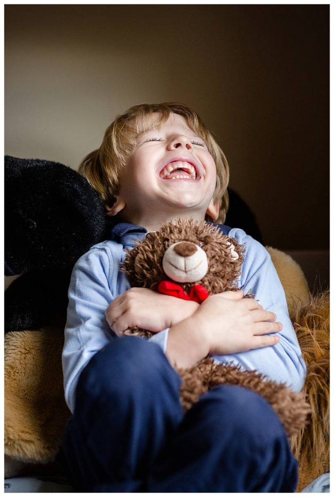 Boy laughing with Teddy