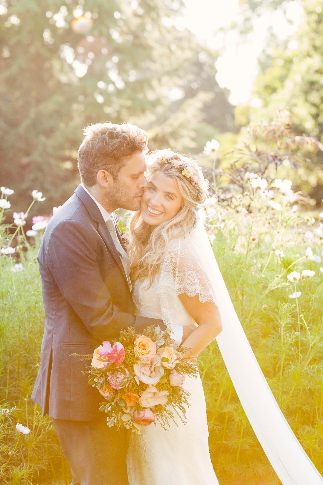 WEdding portraitWedding portrait of groom kissing bride  in wildflower meadow with golden sun