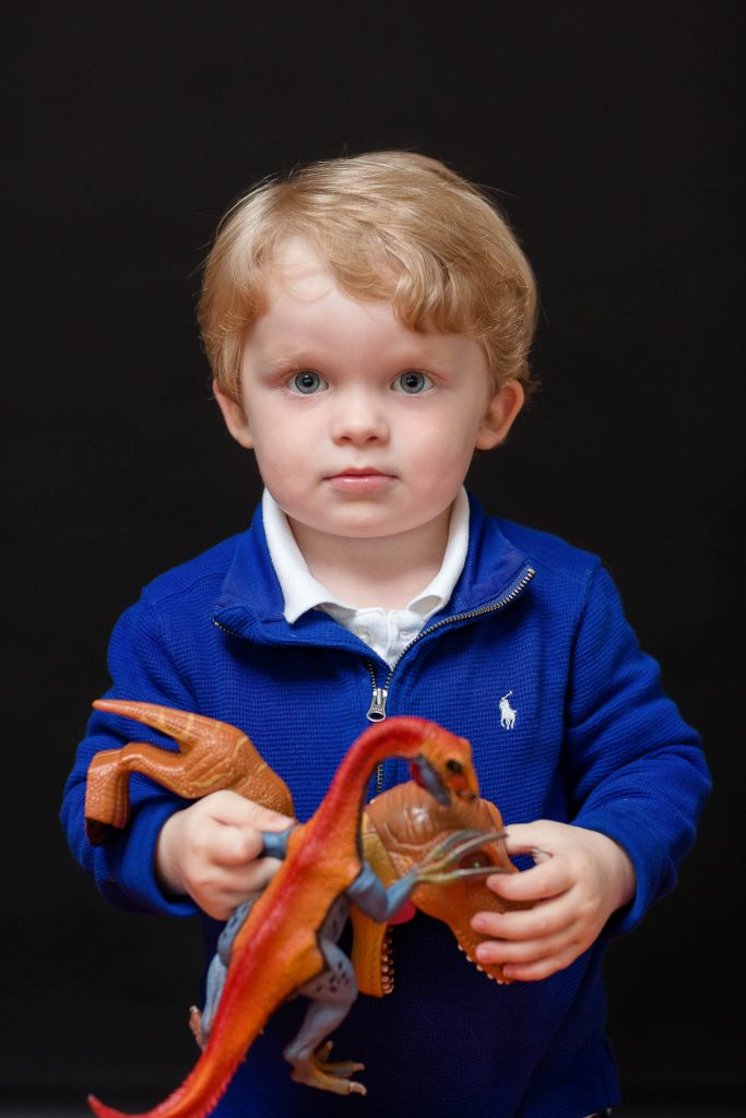 Little boy in blue jumper with dinosaurs