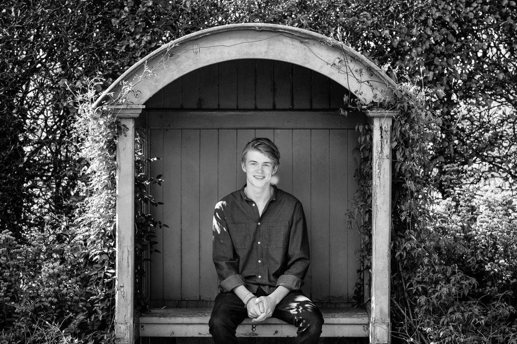 Teenage boy in garden seat