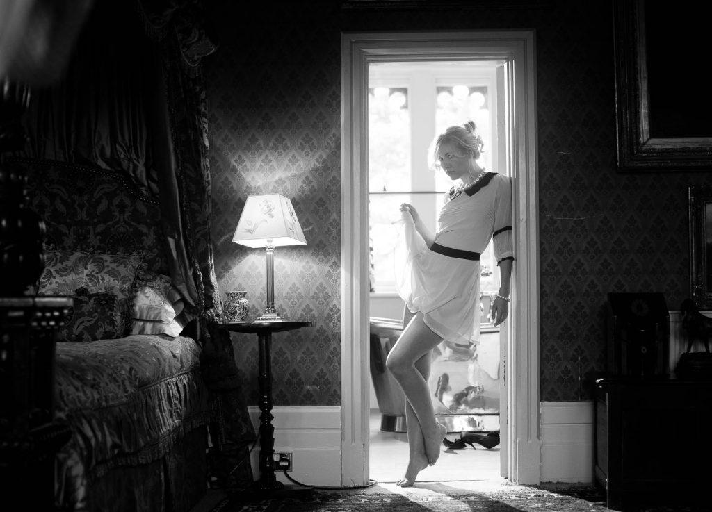 woman in doorway flicking up her skirt flirtatiously