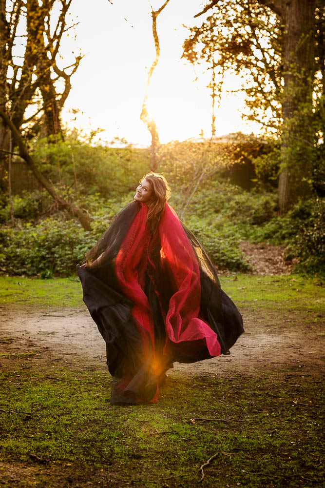 Female portrait photography of Lady in black dress with long red scarf running in Holland Park Portrait shoot