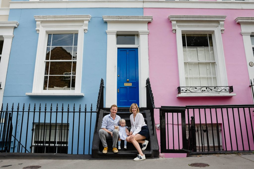 mum dad and baby in front of colourful notting hill houses
