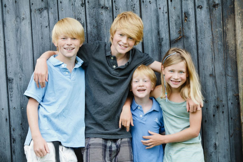 four children against wooden fence