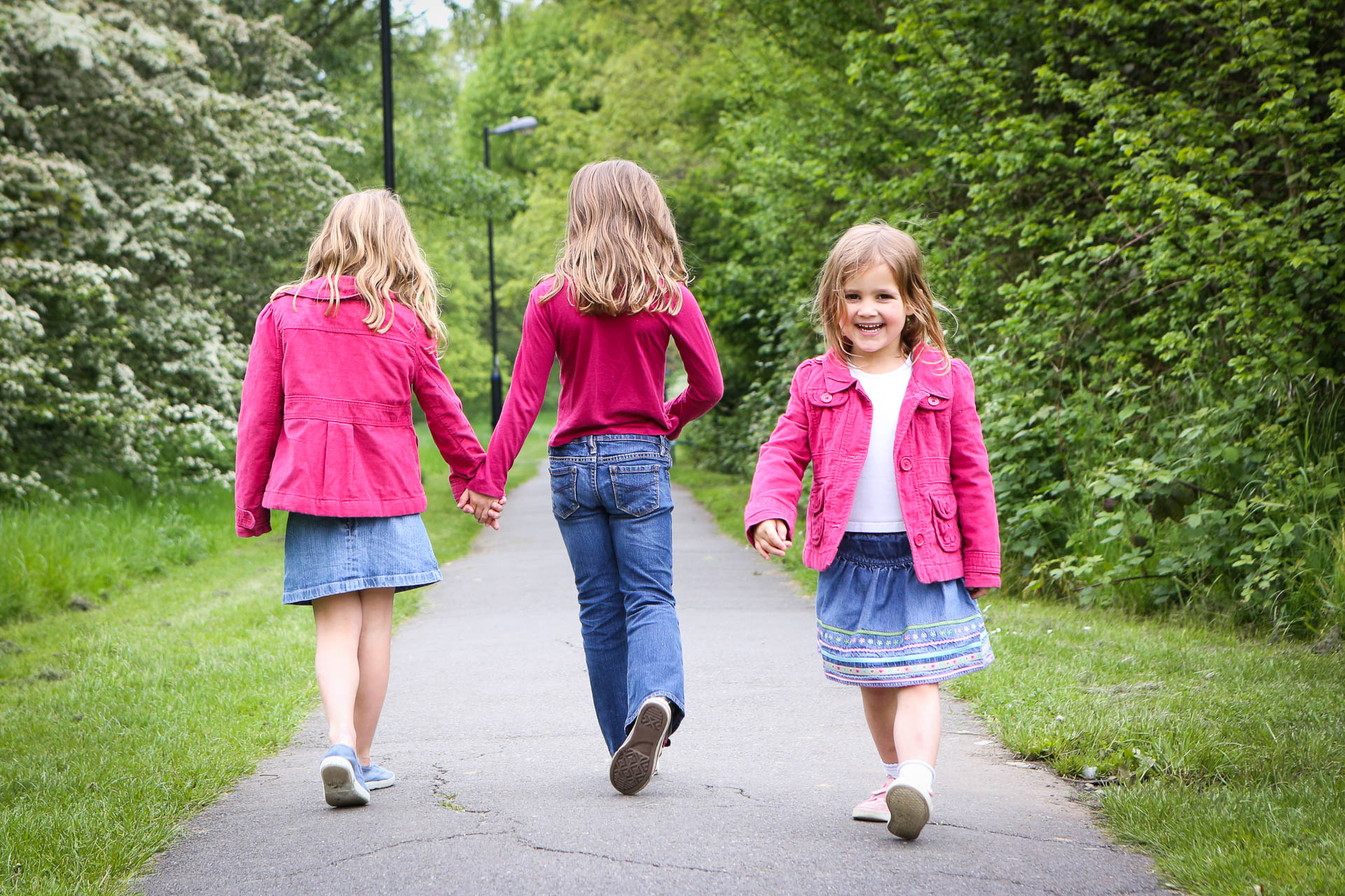 Family photography London three girls in pink walking in the park