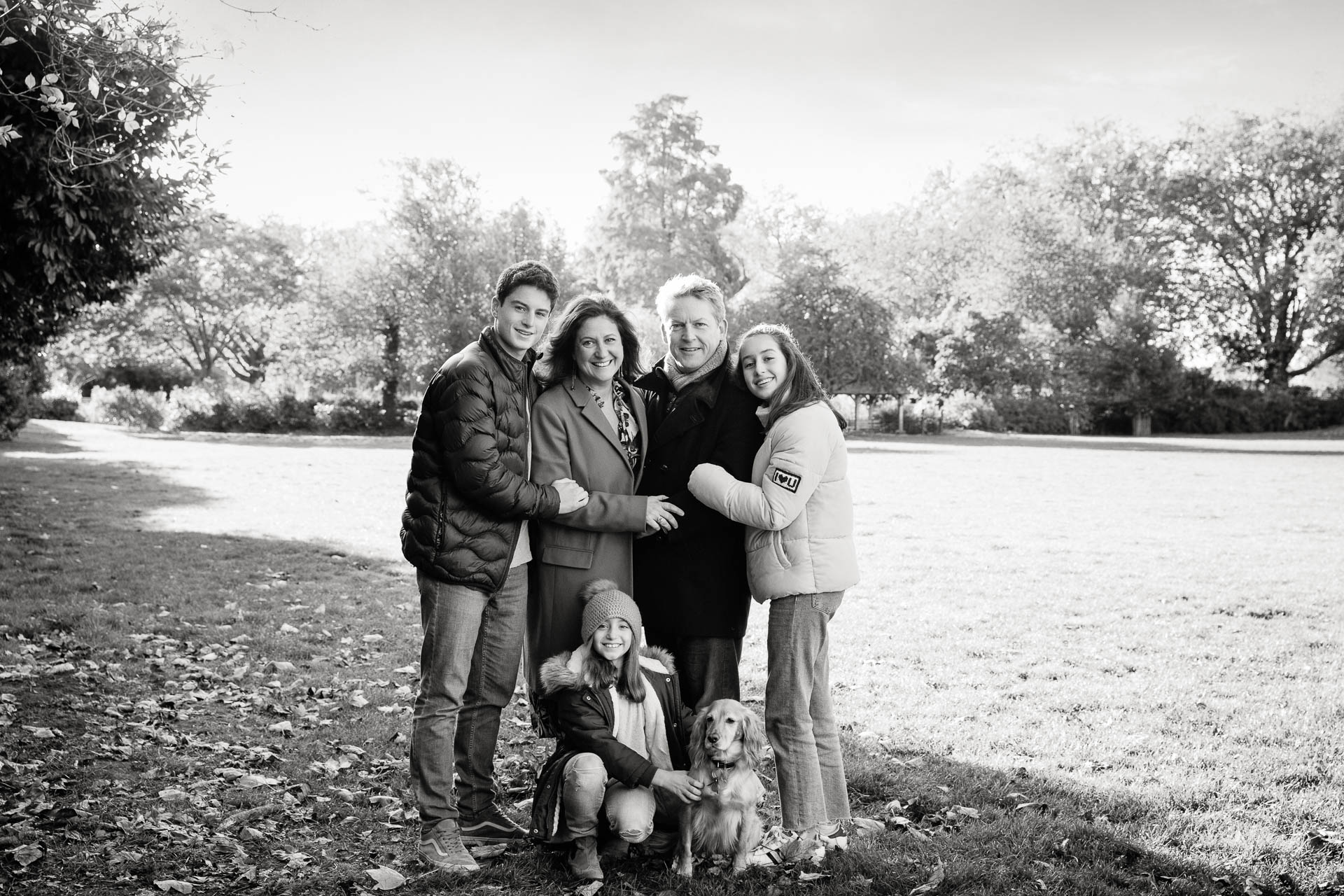 family posing for portrait in west london park with dog