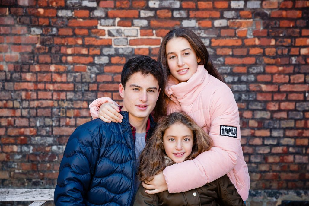 three siblings against brick wall