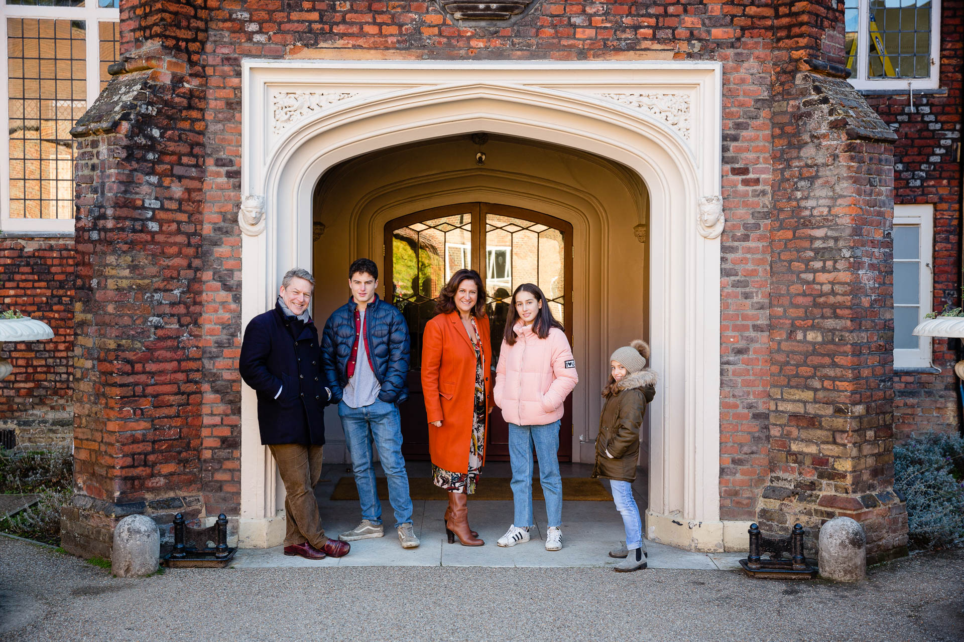 family of 5 posing for family portrait in doorway at Bishop's park