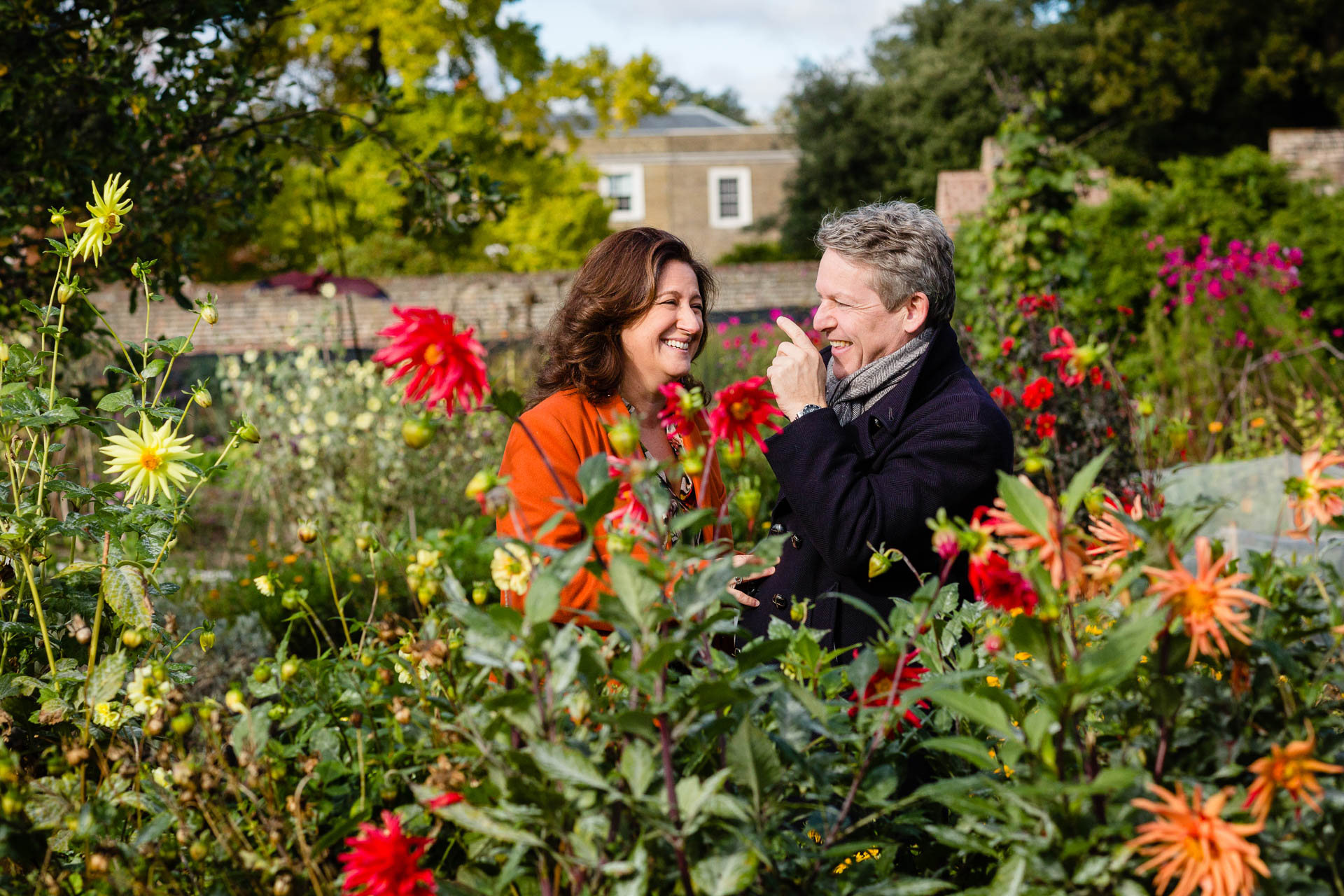 mother and father posing amongst flowers