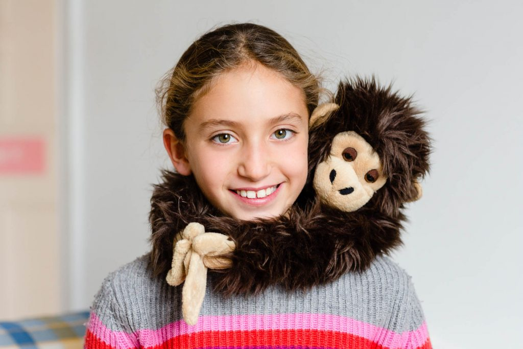 little girl in rainbow jumper with toy monkey