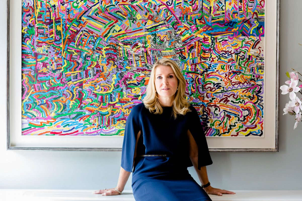 woman in navy dress in front of splatter painting