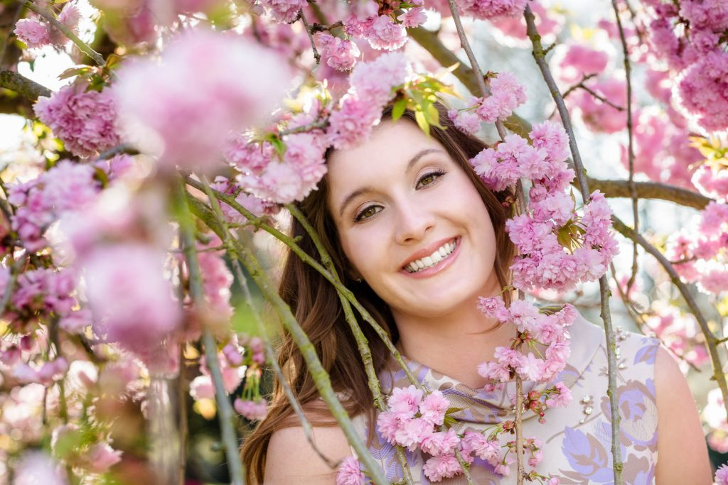 female portait shoot of woman smiling through cherry blossom