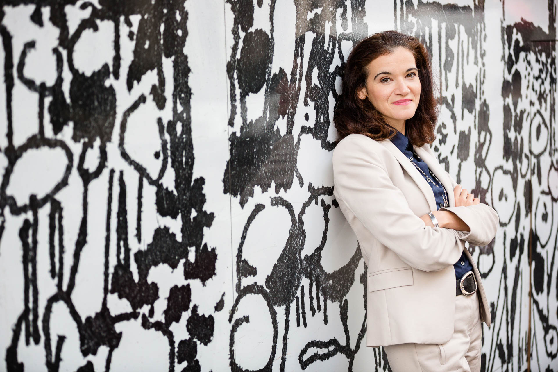Poressional Headshot woman in trousersuit leaning against graffiti wall