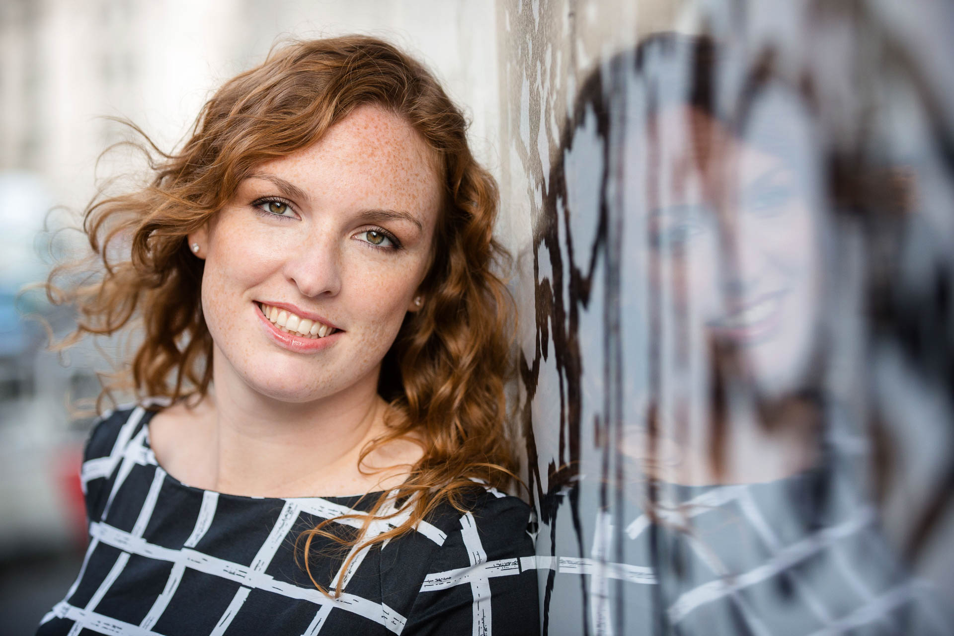 Professional headshot of woman against wall with reflection