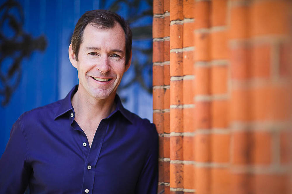 Profesional photo of man in blue shirt leaning on red brick wall