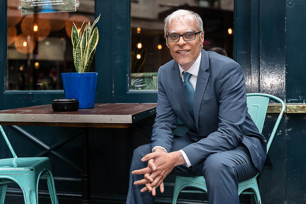 Professional headshot of man in suit at outdoor cafe table