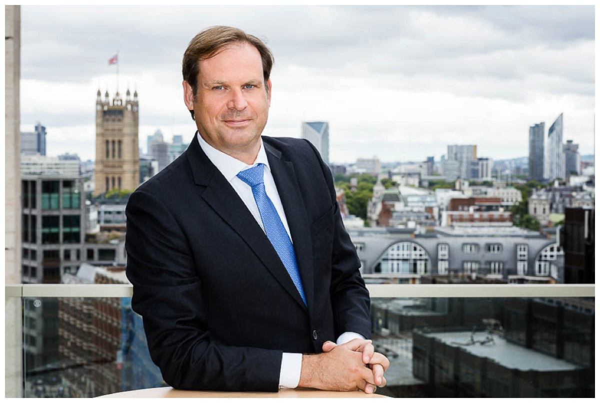 Businessman in suit shown in office against London cityscape
