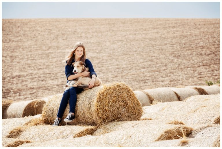 teenage photography of girl with dog on haystack