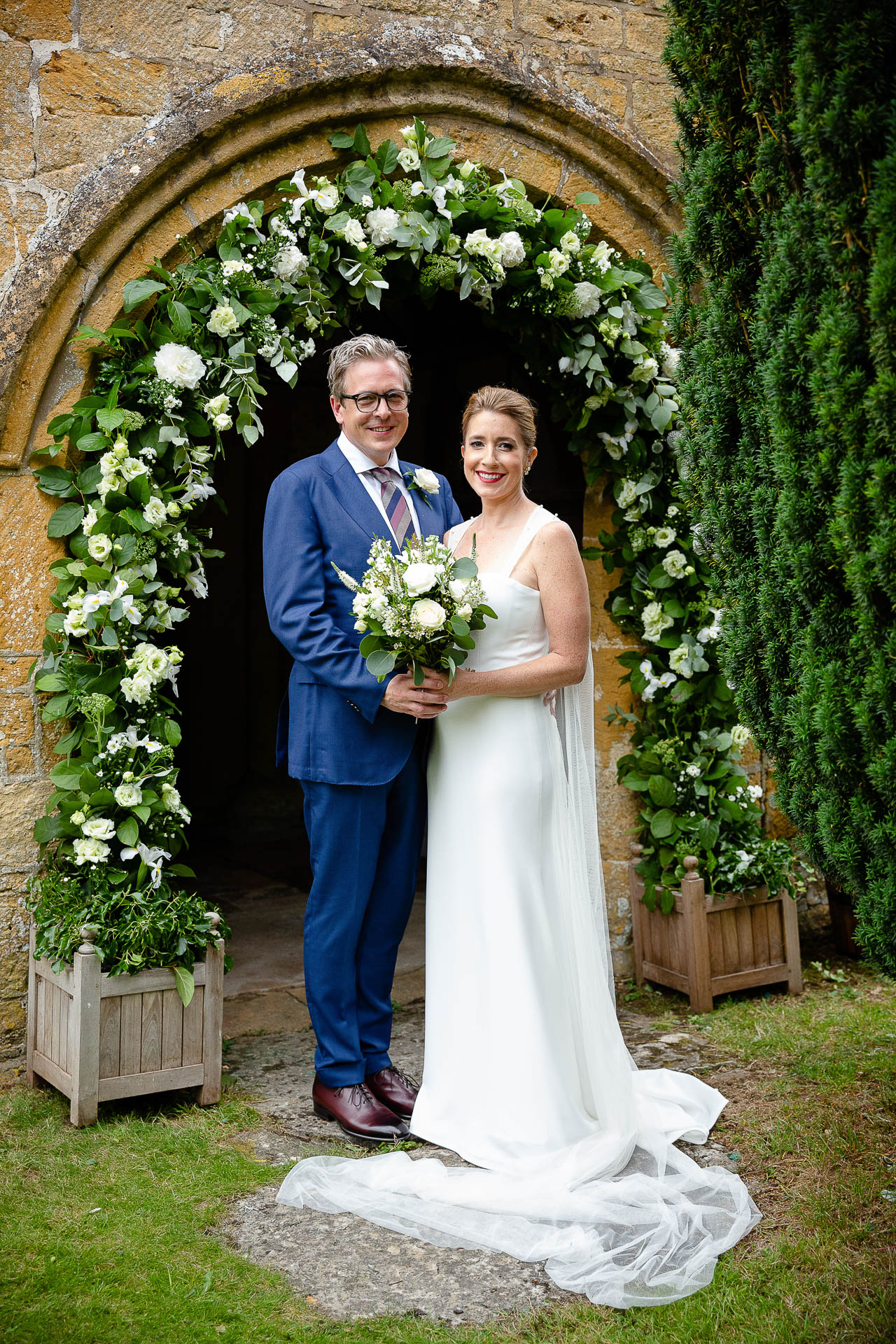 portrait of bride and groom in front of arched chuch doorway with flowers