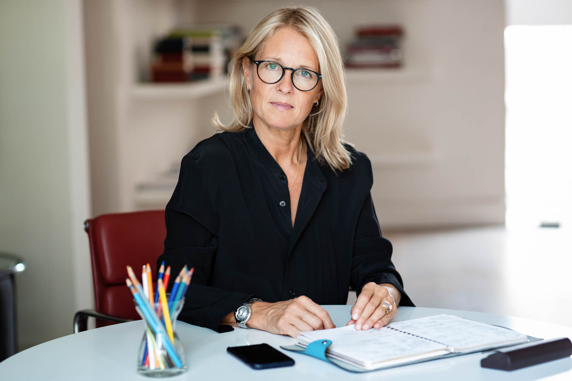 Blonde businesswoman sitting at desk with coloured pencils