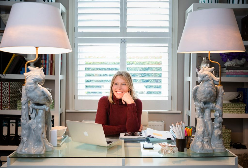personal brand photography lady in burgandy jumper at her desk with two lamps