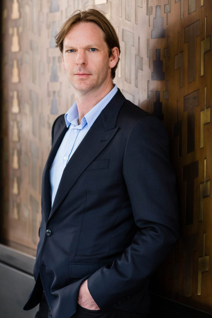 personal brand photography man leaning against wall in suit