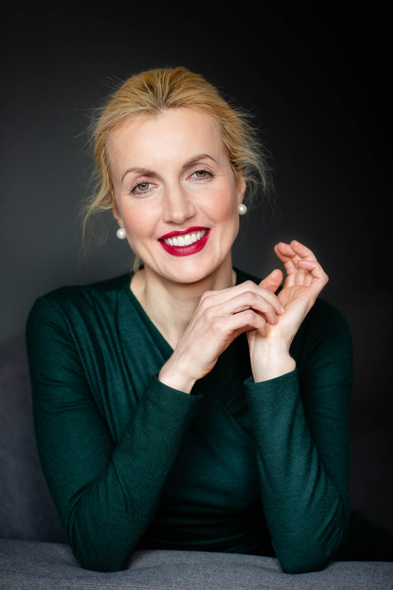 studio headshot of blonde lady in green dress