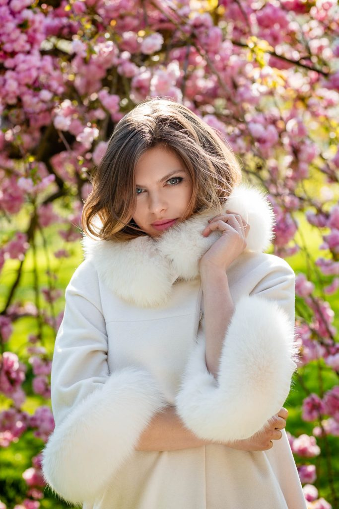 female portrait photo of a young woman peeping out of white fur collared coat with blossoms in background