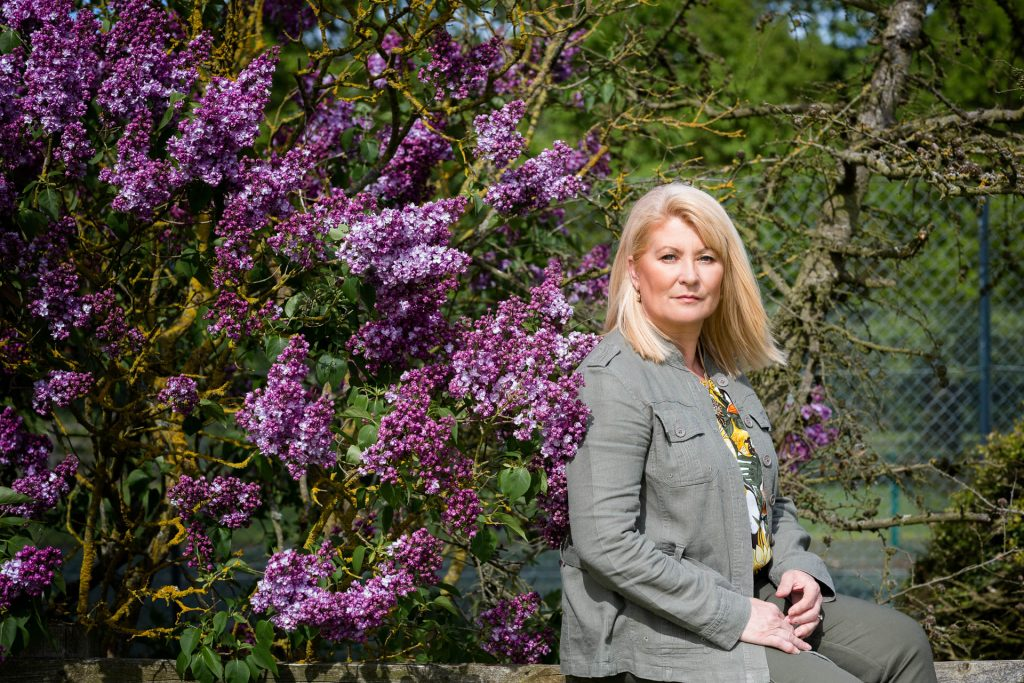 personal brand photography blonde woman in suit next to purple bushes