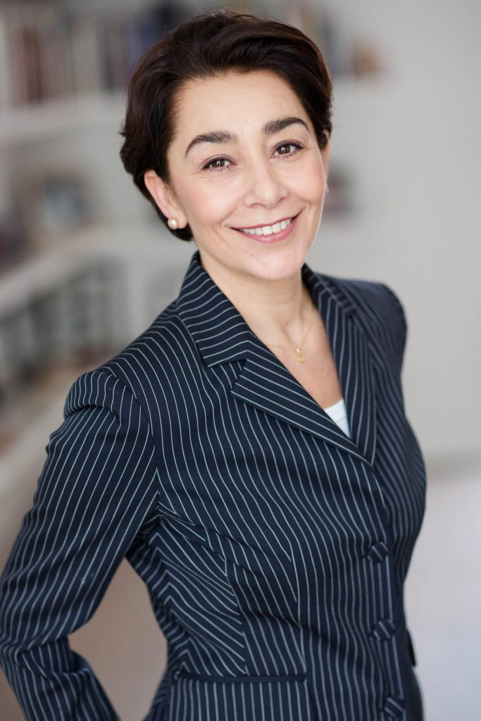 headshot of smiling woman in pinstripe business suit