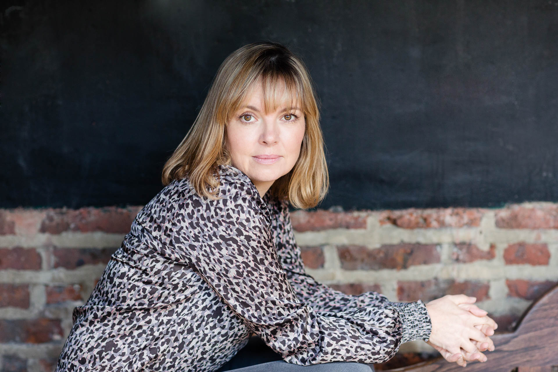 personal brand photography woman in leopard print against brick wall on bench