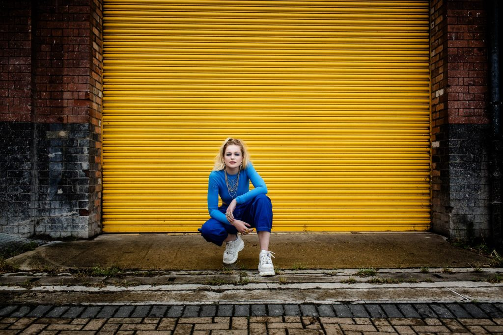 young adult woman in blue with blonde ponytail in front of yellow garage door
