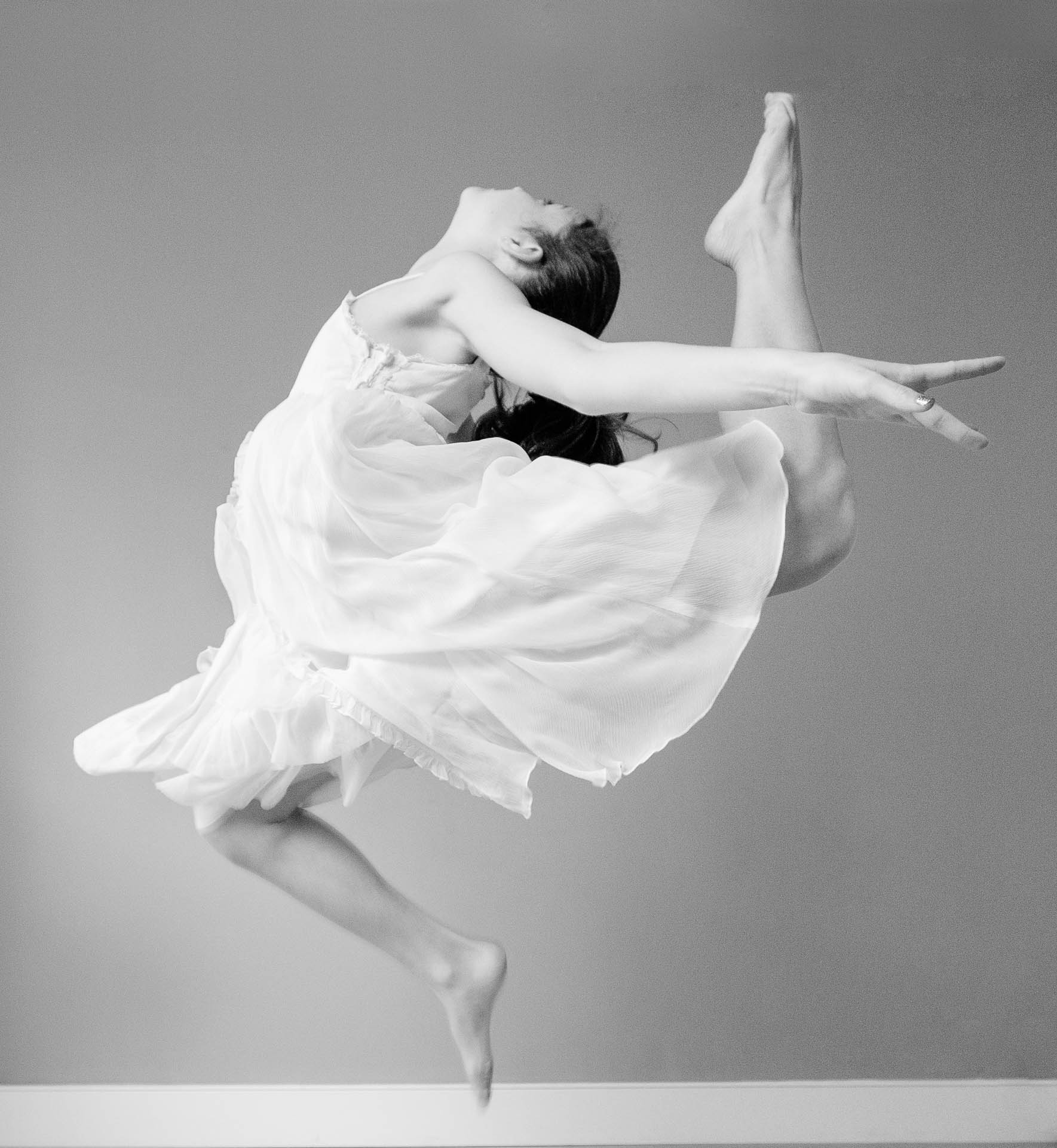teenage photography girl in white dress leaping through air
