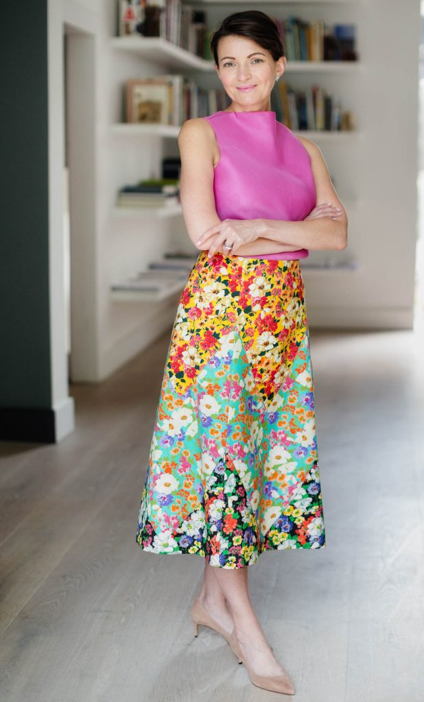 studio portrait of businesswoman in pink top and floral skirt