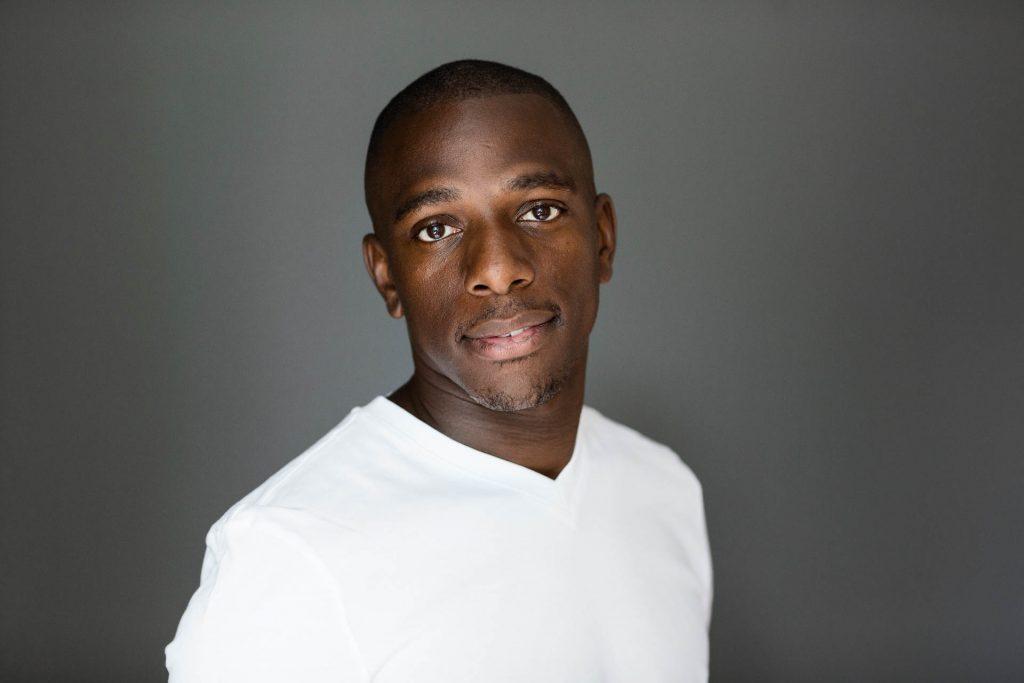headshot of man in white t shirt against dark background