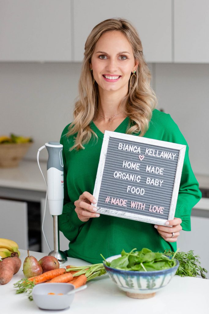 Blonde lady in green shirt holding up sign for her business