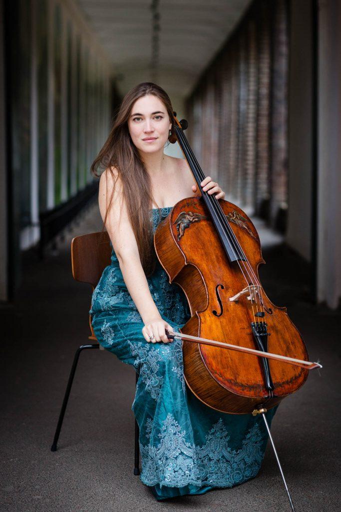 Portrait of cellist in evening dress in colonnaded backdrop
