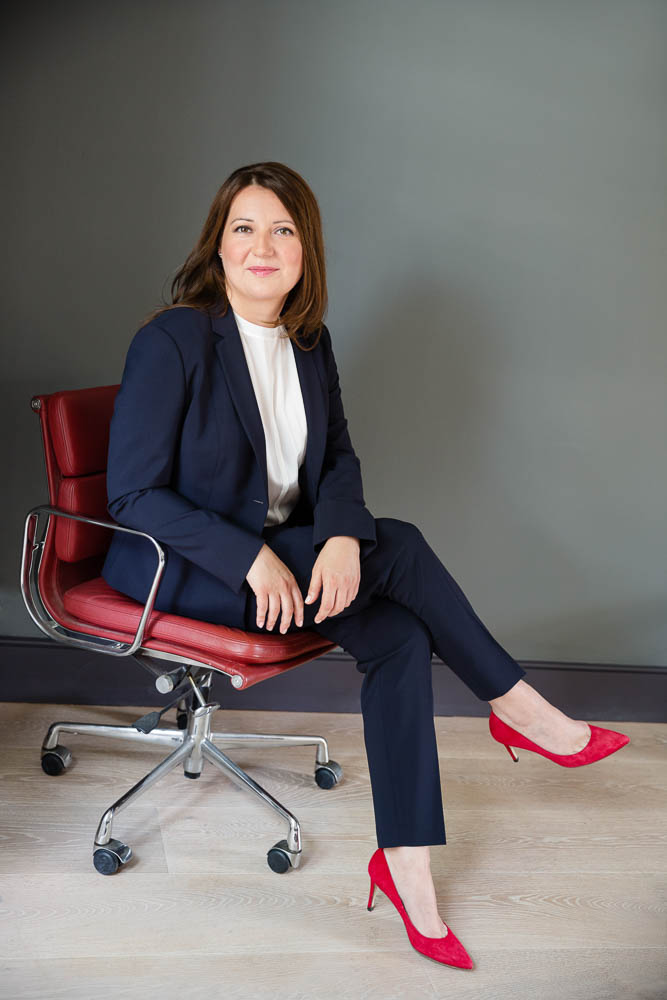 businesswoman in red shoes on red chair in studio portrait
