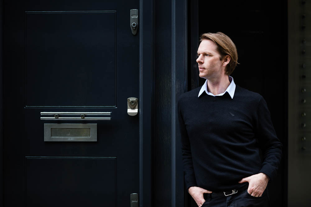 businessman portrait in profile in front of a black door