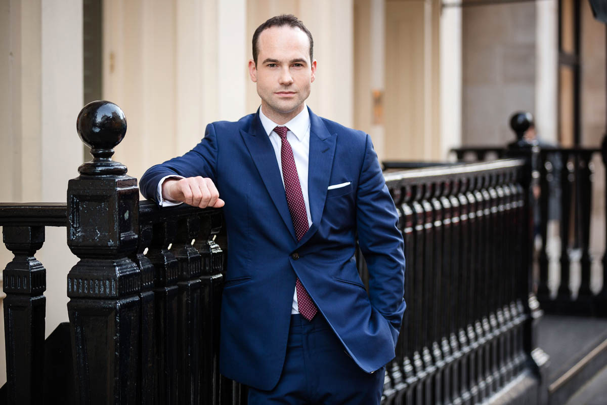 corporate portrait of man leaning on railings
