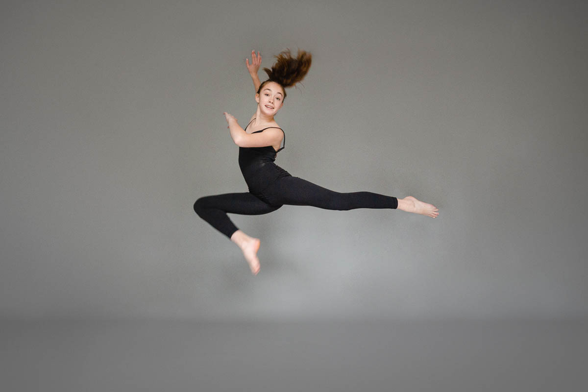 photograph of young dancer leaping through air