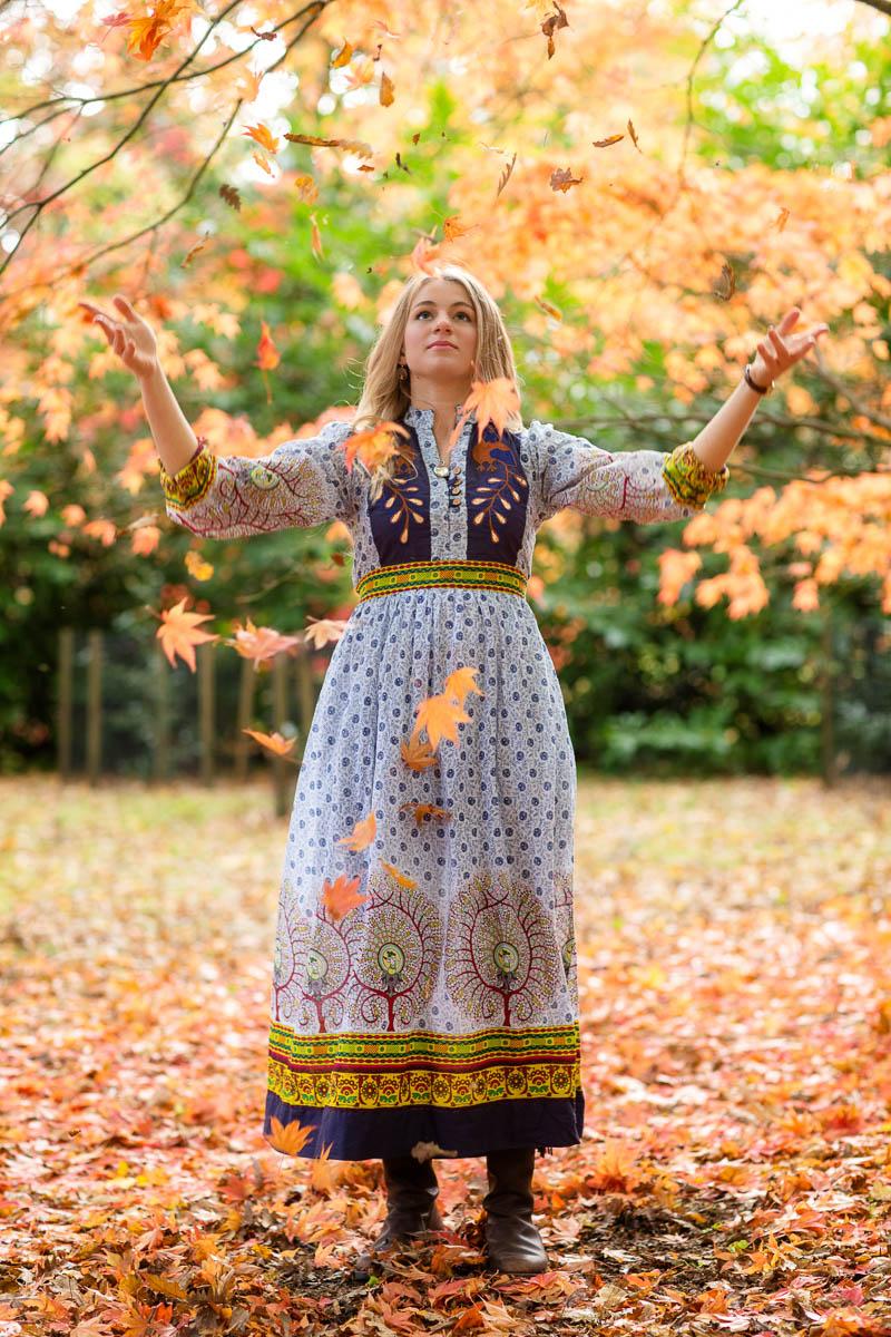 Portrait of a women amongst leaves in blue dress