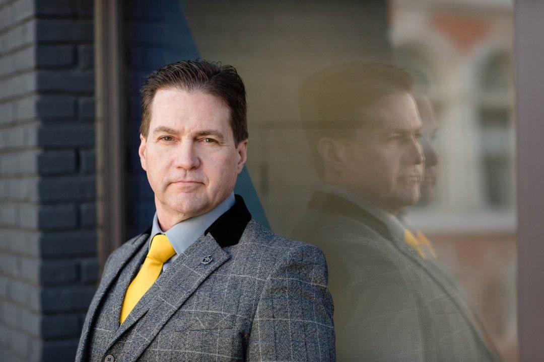 headshot of man with yellow tie